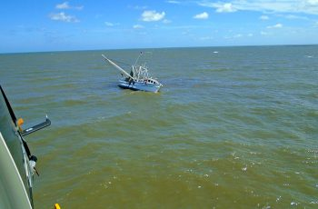 Responders aboard a Coast Guard Air Station Savannah MH-65 Dolphin helicopter approach the Lady Vanessa, which began taking on water May 18, 2017, near St. Simons Island, Ga. Three fishermen were rescued safely. USCG photo.