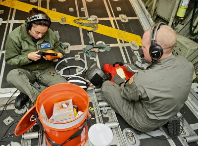 Aviation maintenance technicians from Coast Guard Air Station Barbers Point, Hawaii, prepare a long range deployable drop kit including food and water, a VHF radio, and a transponder to a disabled vessel approximately 80 miles off Tonga May 25, 2017. USCG photo.