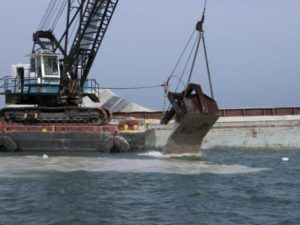 Limestone being deployed by barge on an inshore artificial reef site. Louisiana Department of Wildlife and Fisheries photo.