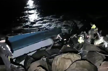 The first crewman to emerge from the overturned Pacific Miner reaches the top of a Coos Bay jetty after firefighters sawed a hole in the hull. Video still courtesy Basin Tackle Charleston.